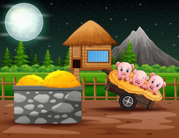 Nocny krajobraz farmy z trzema małymi świnkami na wózku