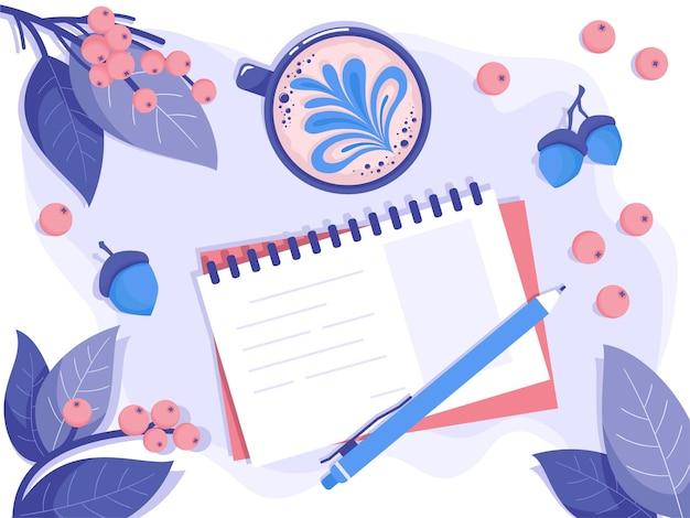 Notatnik i długopis leżą na stole w liściach i jagodach obok sztuki latte