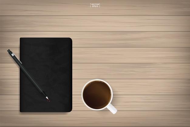 Notatnik z czarną okładką tekstury i filiżankę kawy na tle drewna.