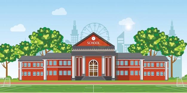 Nowoczesna szkoła z boiskiem do piłki nożnej przed budynkiem szkoły.