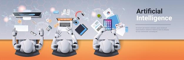 Nowoczesne roboty siedzące w zespole humanoidów w miejscu pracy pracujące ze sztuczną inteligencją urządzeń cyfrowych