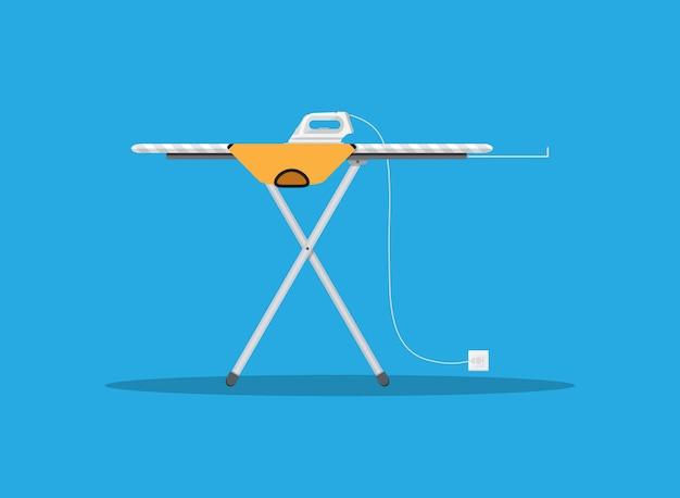 Nowoczesne żelazko i pomarańczowa koszulka na desce do prasowania
