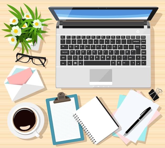 Nowoczesny zestaw do pracy z drewnianym stołem, laptopem, notatkami, filiżanką kawy, tabletem, okularami, długopisem, kopertą, kwiatami.