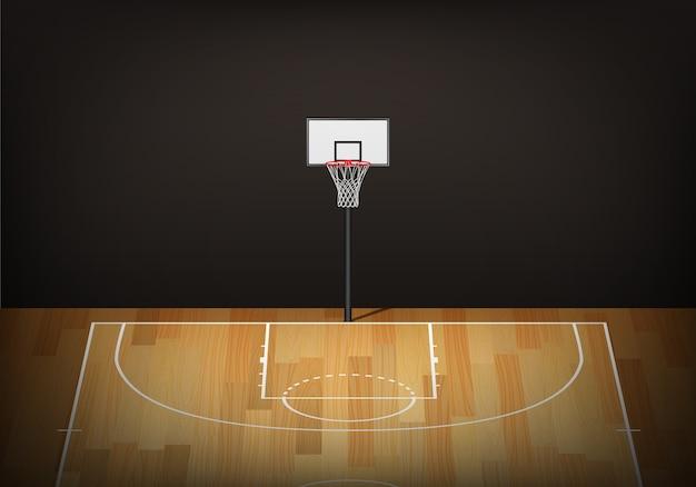 Obręcz do koszykówki na pustym drewnianym korcie.