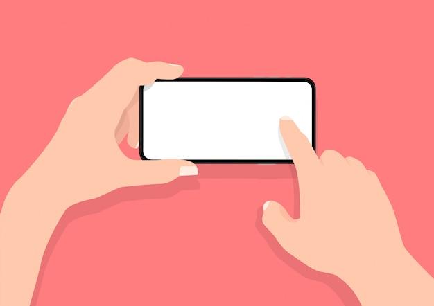 Obsługuje dwie ręce trzyma mobilnego mądrze telefon w horyzontalnej pozyci z pustym ekranem.