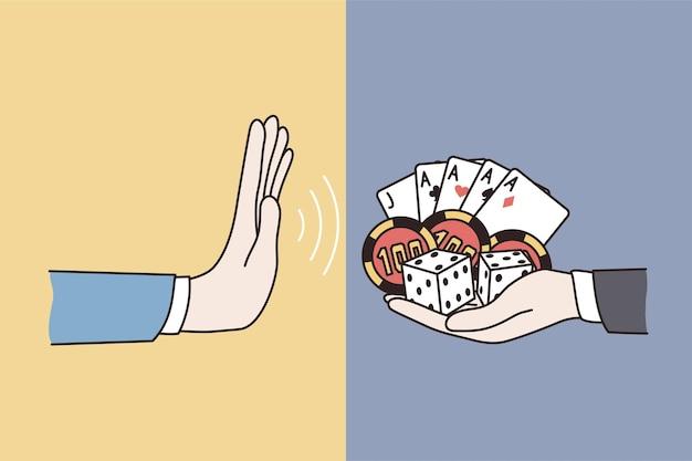 Odmowa koncepcji stylu życia hazardu. ludzka ręka nie odmawiająca znaku z innej ręki trzymająca karty i żetony
