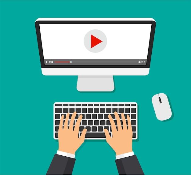Odtwarzacz wideo na monitorze. streaming tv, oglądanie treści wideo. ręce piszą. widok z góry.