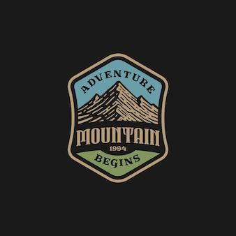 Odznaka z logo góry i przygody w stylu vintage.