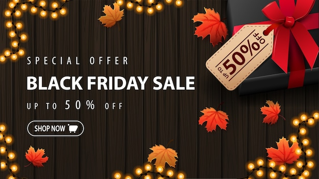 Oferta specjalna, wyprzedaż black friday, do 50% zniżki, baner rabatowy z dużym prezentem z ceną z ofertą i liśćmi klonu na drewnianym tle, widok z góry