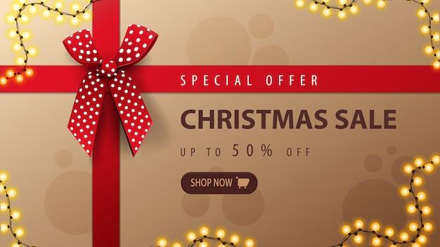 Oferta specjalna, wyprzedaż świąteczna, baner rabatowy w formie pudełka na prezenty z czerwoną wstążką i kokardką, widok z góry
