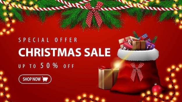 Oferta specjalna, wyprzedaż świąteczna, do 50% taniej, piękny czerwony sztandar rabatowy z gałęziami choinek, girlandami i torbą świętego mikołaja z prezentami