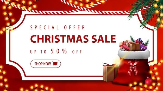 Oferta specjalna, wyprzedaż świąteczna, do 50% zniżki, czerwony baner rabatowy z białą kartką papieru w formie biletu w stylu vintage, gałęziami choinek, girlandami i torbą świętego mikołaja z prezentami