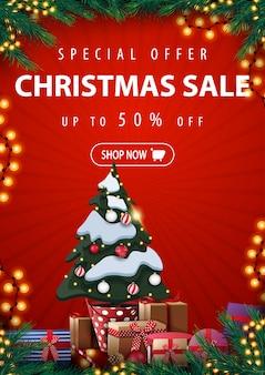 Oferta specjalna, wyprzedaż świąteczna, do 50% zniżki, czerwony pionowy baner rabatowy z choinką w doniczce z prezentami, ramką z gałęzi choinki, girlandami i prezentami