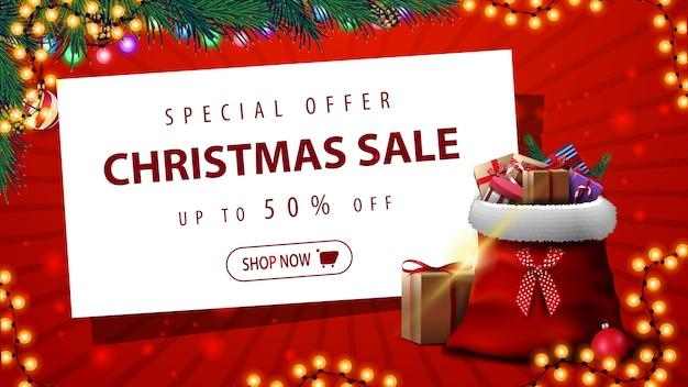 Oferta specjalna, wyprzedaż świąteczna, do 50% zniżki, czerwony sztandar rabatowy z girlandą, choinka, biała kartka papieru i torba świętego mikołaja z prezentami