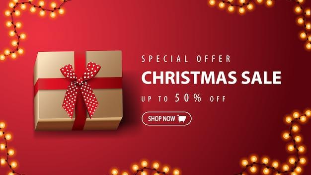 Oferta specjalna, wyprzedaż świąteczna, do 50% zniżki, czerwony sztandar rabatowy z prezentem z czerwoną kokardą na czerwonym tle
