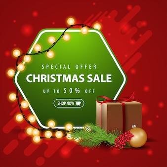 Oferta specjalna, wyprzedaż świąteczna, do 50% zniżki, kwadratowy czerwony i zielony sztandar z girlandą, prezentem i gałęzią choinki