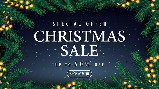 Oferta specjalna, wyprzedaż świąteczna, do 50% zniżki, niebieski baner rabatowy z niebieskim gwiaździstym niebem, duży tytuł i ramka oraz gałęzie i girlandy choinkowe