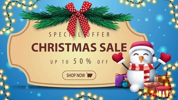 Oferta specjalna, wyprzedaż świąteczna, do 50 zniżki, niebieski baner rabatowy z ramką vintage, gałązki choinki z czerwoną kokardką, girlanda i bałwan w czapce świętego mikołaja z prezentami