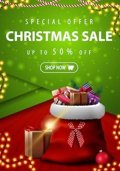 Oferta specjalna, wyprzedaż świąteczna, do 50% zniżki, pionowy czerwony i zielony sztandar rabatowy w materialnym stylu z torbą świętego mikołaja z prezentami