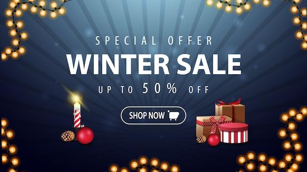 Oferta specjalna, wyprzedaż zimowa, rabat do 50, ciemnoniebieski baner rabatowy z girlandą i prezentami