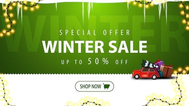 Oferta specjalna, wyprzedaż zimowa, rabat do 50, zielono-biały baner rabatowy z guzikiem, ramka girlandy, sople lodu i czerwony zabytkowy samochód wiozący choinkę