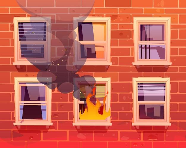 Ogień w oknie domu z długim płonącym płomieniem i czarną parą w budynku