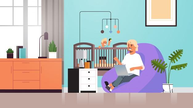 Ojciec freelancer pracuje w domu za pomocą laptopa synek bawi się zabawkami w łóżeczku podczas kwarantanny