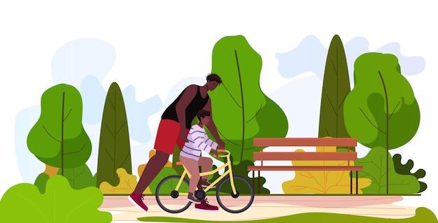 Ojciec uczy małego syna jeździć na rowerze rodzicielstwo koncepcja ojcostwa tata spędza czas z dzieckiem w parku krajobraz tło poziomo długość