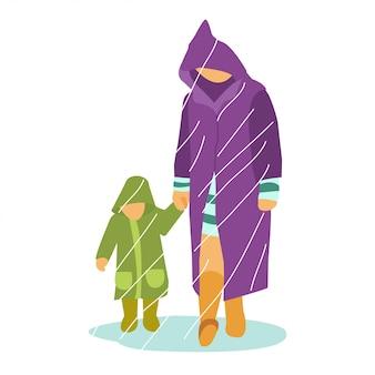 Ojciec z małym dzieckiem bawiącym się w środku pory deszczowej w płaszczu