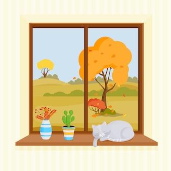 Okno na jasnym tle. za oknem rosną drzewa o żółtych liściach. na parapecie jest bukiet jesiennych liści, kaktusa i śpiącego kota.