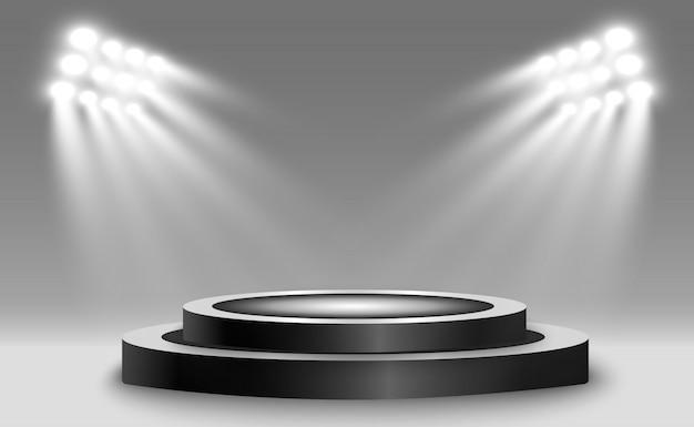 Okrągłe podium, cokół lub platforma, oświetlone reflektorami w tle.