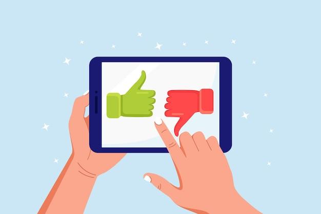 Opinie klientów, ocena i koncepcja recenzji. ludzkie ręce trzymając tablet z sympatią i niechęcią. kciuk w górę iw dół na ekranie komputera. blogi, wiadomości online, serwisy społecznościowe