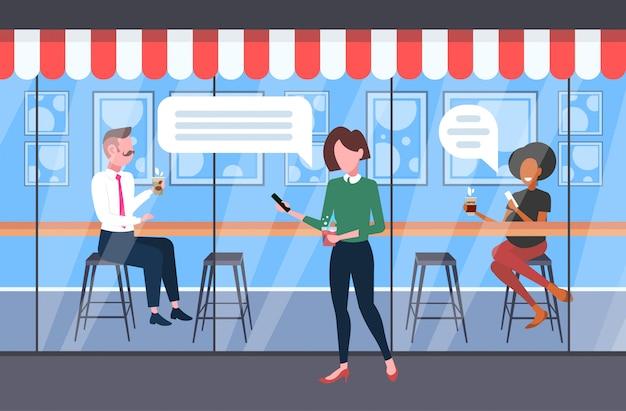 Osoby korzystające z aplikacji mobilnej na czacie czat bańka koncepcja komunikacji w mediach społecznościowych goście piją kawę zabawę nowoczesna kawiarnia uliczna pełnej długości pozioma