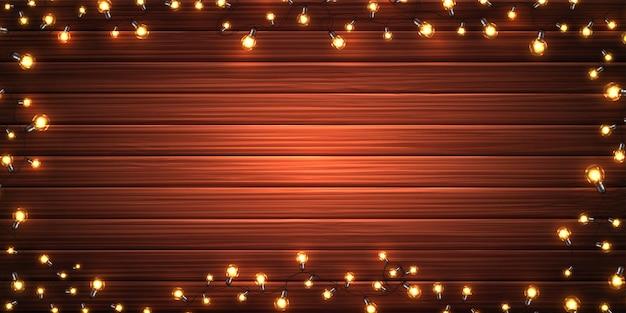 Oświetlenie świąteczne. boże narodzenie świecące girlandy żarówek led na drewniane tekstury. dekoracje świąteczne z realistycznych kolorowych lamp