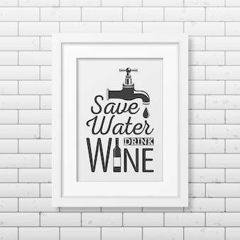 Oszczędzaj wodę, pij wino - cytat typograficzny w realistycznej kwadratowej białej ramce na ścianie z cegły