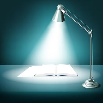 Otwarta książka na stole z lampką biurkową. literatura podręcznikowa, nauka i światło, oświetlone miejsce pracy,