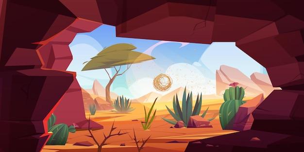 Otwór wejściowy do jaskini pustynnej w skale z kaktusami