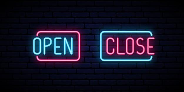 Otwórz i zamknij neonowy napis na tle ceglanego muru.