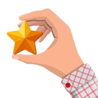 Ozdoba w kształcie gwiazdy w ręku. pięć rogów złota gwiazda. symbol bogactwa, trofeum lub nagrody. ilustracja wektorowa w stylu płaski