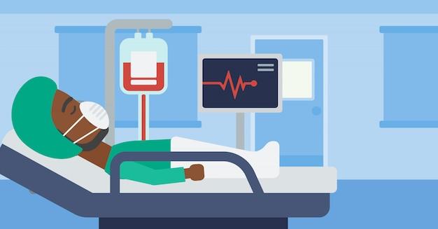 Pacjent leży w szpitalnym łóżku z monitorem serca.