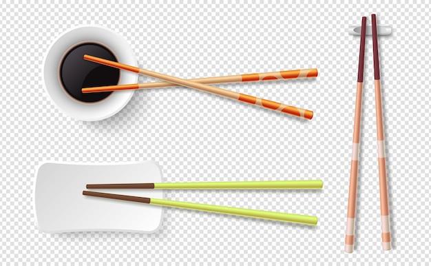 Pałeczki do jedzenia. kolorowe drewniane paluszki do sushi, talerz z sosem sojowym.