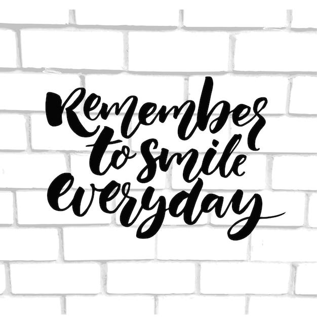 Pamiętaj żeby codziennie się uśmiechać. inspiracja mówiąca kaligrafia na białej ścianie z cegły.