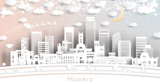 Panoramę miasta madryt hiszpania w stylu cięcia papieru z płatkami śniegu, księżycem i neonową girlandą. ilustracja wektorowa. koncepcja boże narodzenie i nowy rok. święty mikołaj na saniach.
