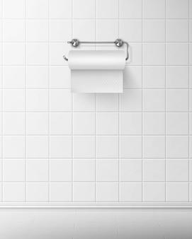 Papier toaletowy na metalowym uchwycie zwisa na kafelkowej ścianie