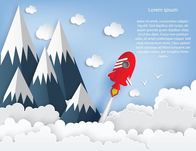 Papierowa grafika przedstawiająca start promu kosmicznego w niebo błękitne niebo wysokie góry puszyste chmury start rakiety