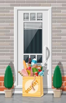 Papierowa torba z zakupami pozostawiona pod drzwiami domu. dostawa jedzenia ze sklepu, kawiarni, restauracji. ekspresowa dostawa produktów spożywczych. chleb, mięso, mleko, warzywa owocowe, napoje. płaska ilustracja wektorowa