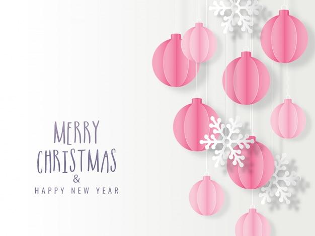 Papierowe bombki wiszą i płatek śniegu dekorowany na białym tle na obchody wesołych świąt i szczęśliwego nowego roku