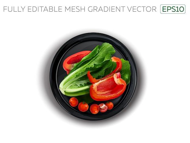 Papryka, sałata i pomidory czereśniowe na czarnym talerzu.