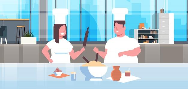 Para kucharzy przygotowuje smaczne posiłki mężczyzna kobieta kucharzy w mundurze wspólne gotowanie nowoczesna kuchnia