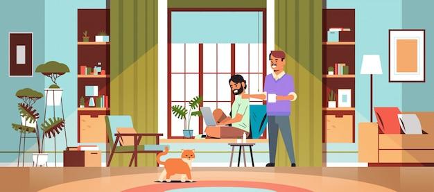 Para mężczyzn korzysta z laptopa, pijąc kawę, spędzając razem czas podczas kwarantanny koronawirusa